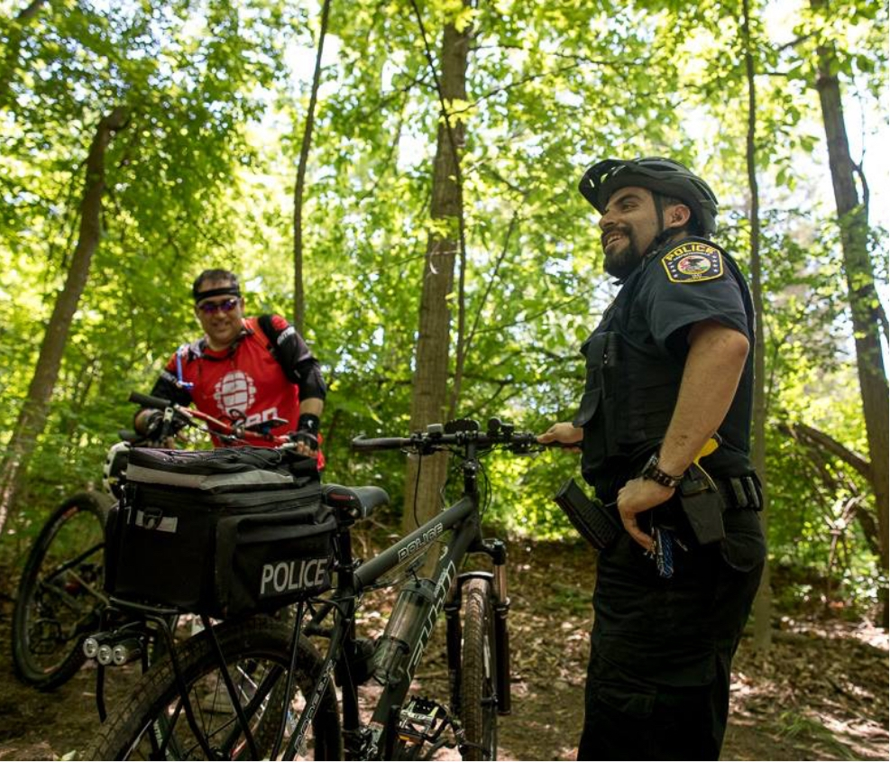 Police officers biking on a park trail