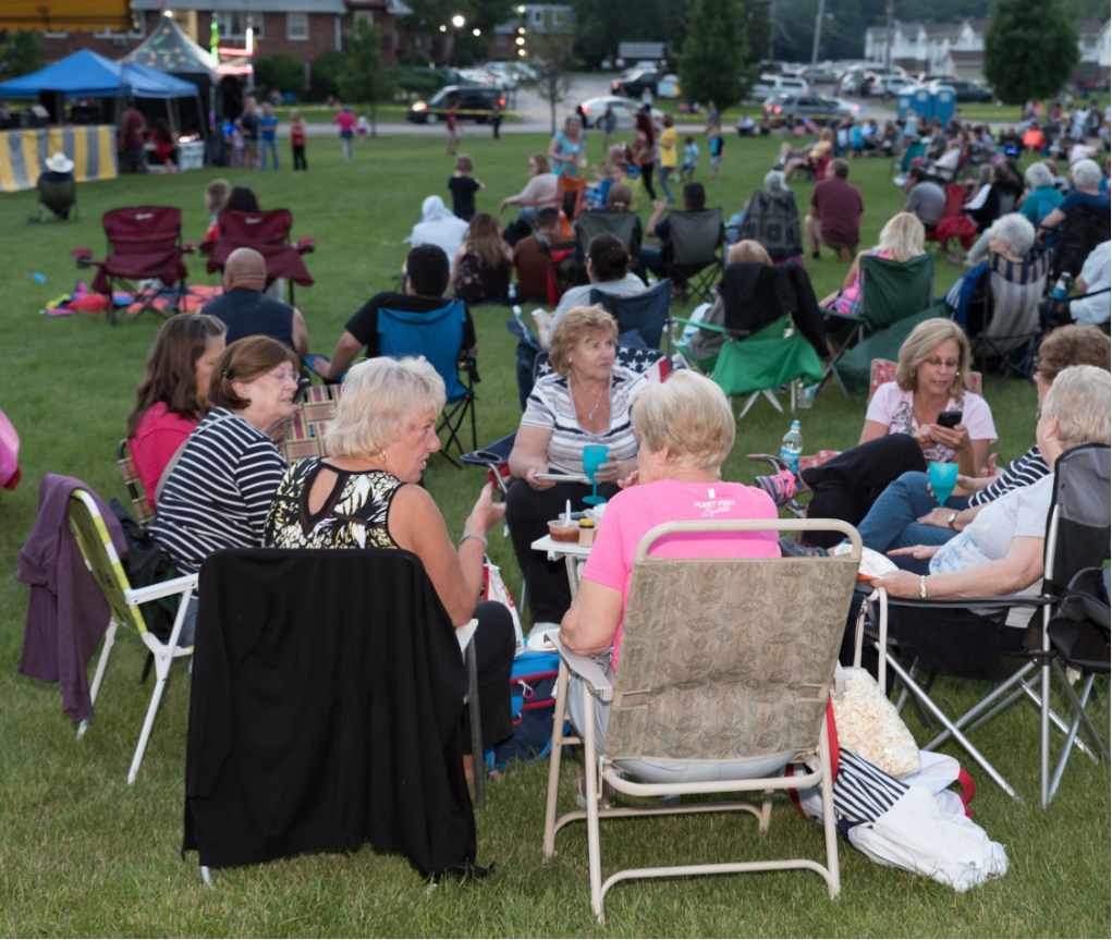 Many families gather in a grassy park
